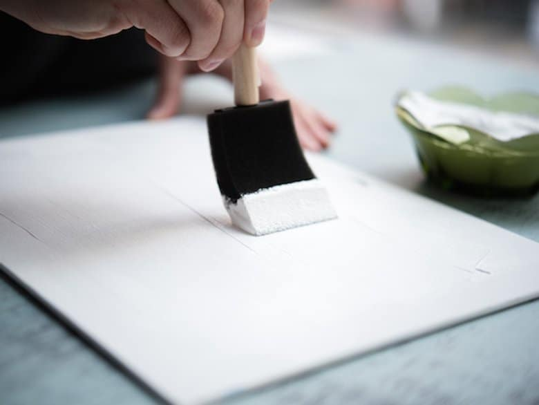 Applying primer on canvas